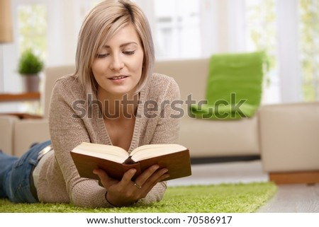 Young blonde woman relaxing on floor at home reading book. Copyspace on right.? - stock photo