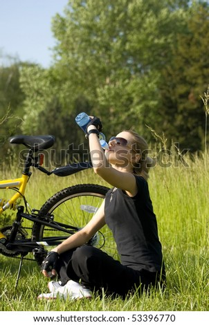 Young blonde  woman resting and drinking water after riding a bike - stock photo