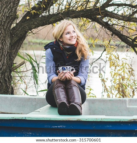 Young blonde woman resting in an old boat and holding a cup of coffee or tea.  - stock photo