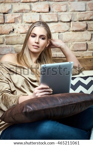 Young blonde woman resting on sofa at home, using tablet computer.