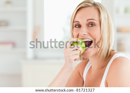 Young blonde woman sitting at table eating a green apple while looking into the camera in the kitchen