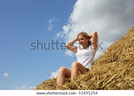 Young blonde woman sitting on a haystack