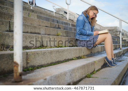 Young blonde woman sitting on stairs and reading book, urban scene