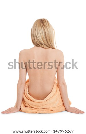 young blonde woman sitting on towel naked back isolated on white background