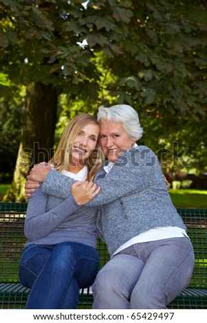 Young blonde woman sitting with her grandmother on a park bench - stock photo