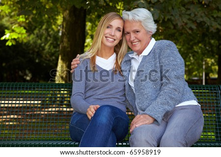 Young blonde woman sitting with her grandmother on a park bench