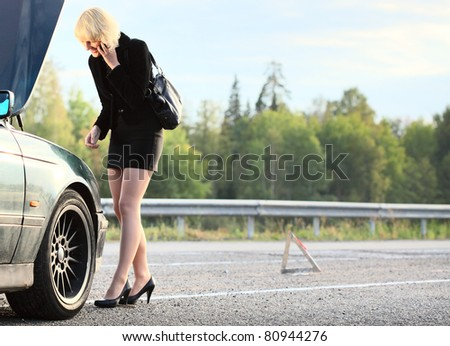 Young blonde woman standing by broken car and calling with cell phone - stock photo