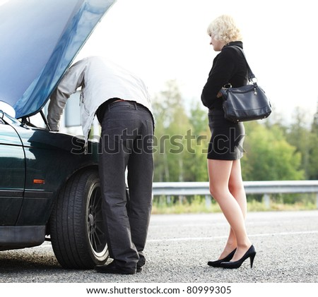 Young blonde woman standing by broken car and waiting her boyfriend - stock photo