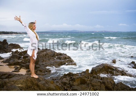 Young blonde woman standing on a big stone of coastline at sunset time.