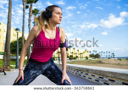 Young blonde woman stretching while listening to music - stock photo