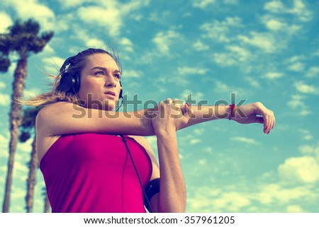Young blonde woman stretching while listening to music in pastels colors - stock photo
