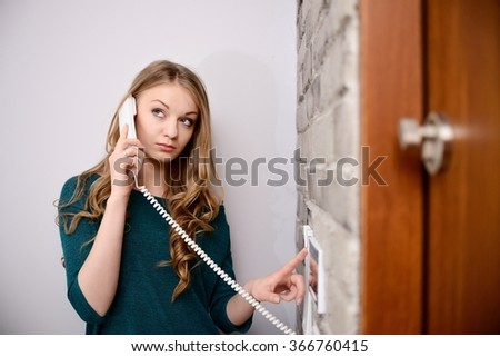Young blonde woman talking on the intercom and presses the button to open the door - stock photo
