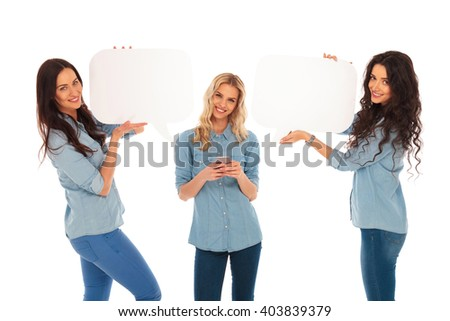 young blonde woman texting on her phone and her friends are holding speech bubbles near her on white studio background - stock photo