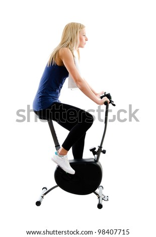 Young blonde woman training on exercise bike in gym