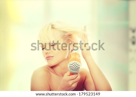 Young blonde woman using hair drier - stock photo