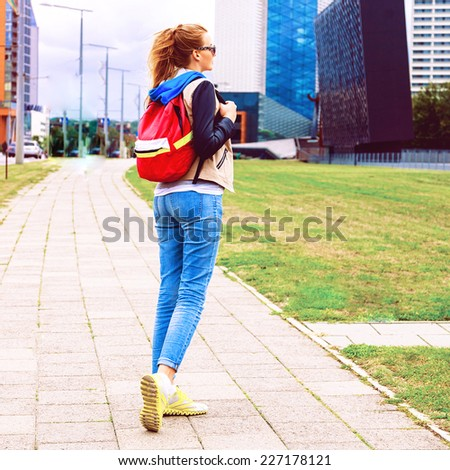 Young blonde woman walking alone, traveling with backpack exploring new city, wearing bright sportive casual clothes, urban background, lifestyle fall portrait of traveller. - stock photo