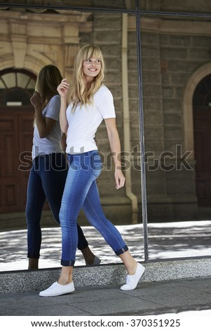 Young blonde woman walking in town, smiling