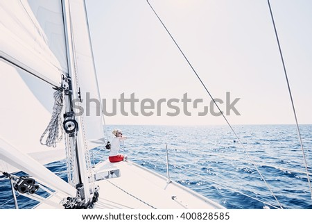 Young blonde woman wearing sunglasses and red shorts, sitting on deck under sails on yacht bow and enjoying wonderful view to peaceful sea during summer sailing holidays - yacht charter concept - stock photo
