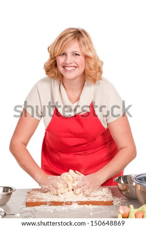 young blonde woman with a red apron kneading dough