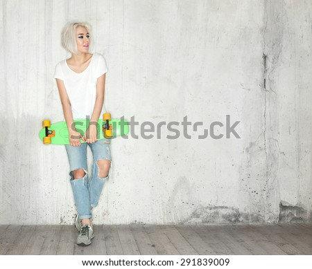 Young blonde woman with a skateboard in his hand against the background of a concrete wall - stock photo