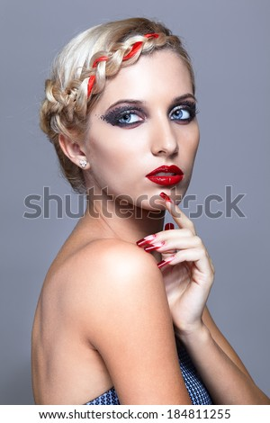 Young blonde woman with braid hairdo and red nails on gray background - stock photo