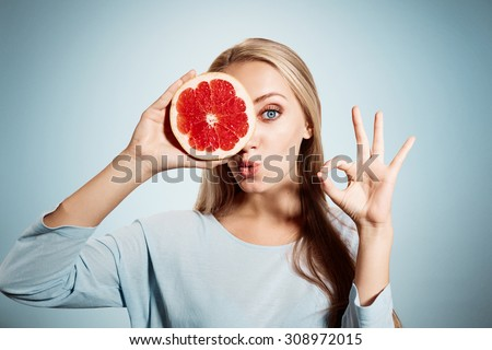 Young blonde woman with grapefruit in her hands studio portrait isolated on blue background. Young blond woman showing OK sign about the benefits of vitamin C - stock photo