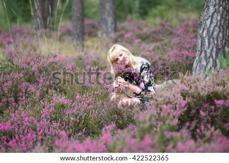 Young  blonde woman with heather flowers,youth and beauty,dreamlike atmosphere