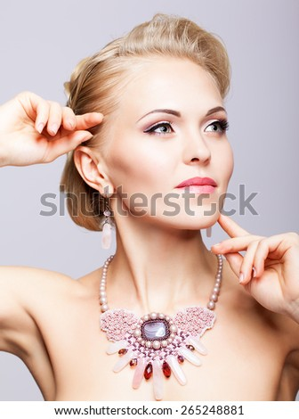 Young blonde woman with necklace - stock photo