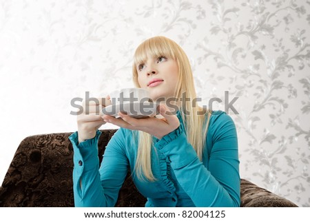 Young blonde woman with tea cup sitting on sofa and thinking looking up