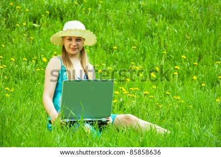 Young blonde woman working with laptop outdoor