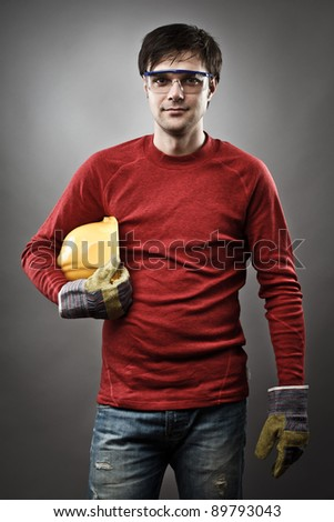 Young blue collar worker with yellow protective helmet and gloves - stock photo