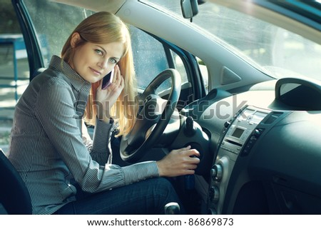 Young blue-eyed businesswoman talking on the cell phone inside her car - stock photo