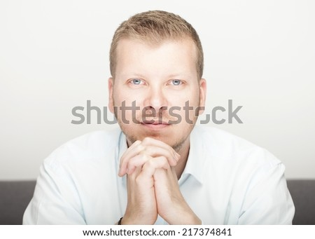 Young blue eyed man sitting with his chin resting on his hands looking directly into the lens with an intent sincere expression - stock photo