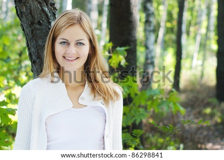 young blue-eyed smiling woman in white against blurred forest background with selective focus and copy space - stock photo