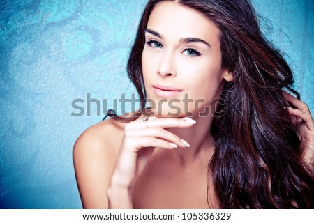 young blue eyes brunette beauty woman portrait on blue background - stock photo