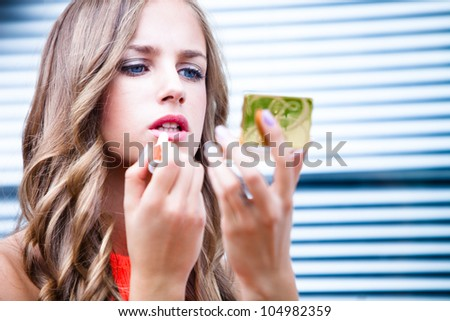 young blue eyes woman  apply lipstick, close up, outdoor shot - stock photo