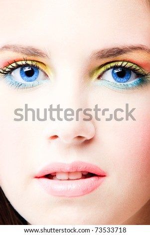 young blue eyes woman close up face with colorful make up, studio shot