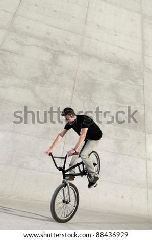 Young BMX bicycle rider on a grey urban concrete background - stock photo