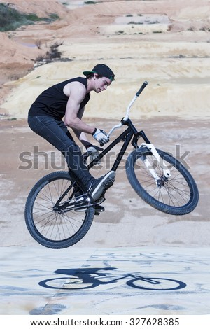 young BMX rider doing a bike trick on a BMX session in the mountain - focus on the face - stock photo