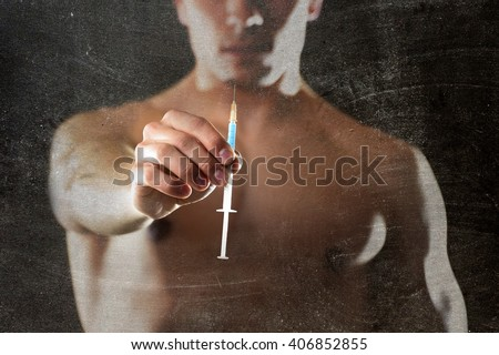 young body building sportsman using steroids for increasing sport and athletic  performance holding syringe isolated on back background in sport cheat doping and illegal use of hormones - stock photo