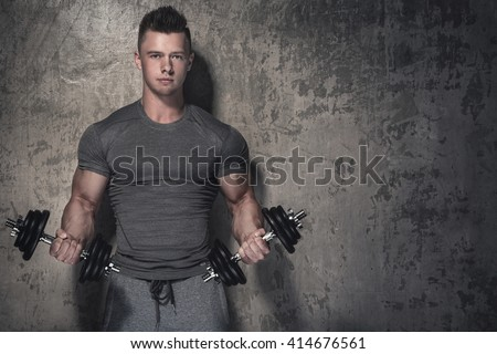 Young bodybuilder doing biceps curls with dumbbells