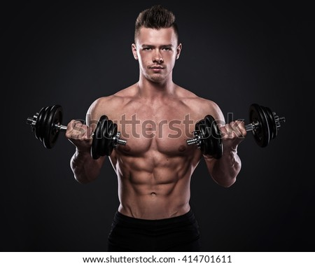Young bodybuilder doing exercises with dumbbells - stock photo