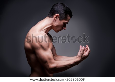 Young Bodybuilder Flexing Muscles - stock photo