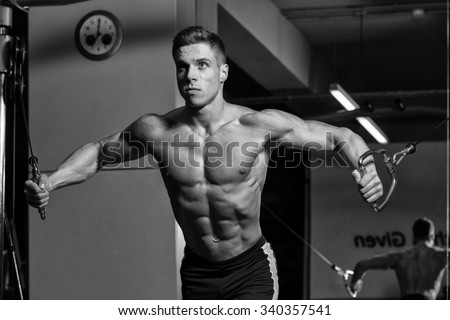 Young Bodybuilder Is Working On His Chest With Cable Crossover In A Dark Gym - stock photo