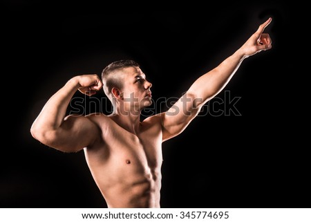 young bodybuilder man pointing isolated on black background - stock photo