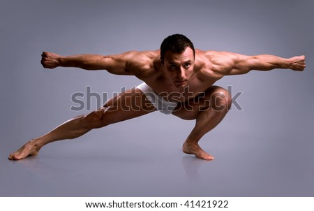 Young bodybuilder man posing on grey background. - stock photo