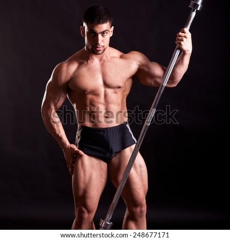 young bodybuilder posing in studio - stock photo
