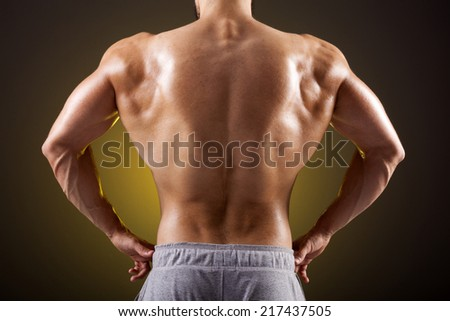 Young bodybuilder showing his back on a dark background - stock photo