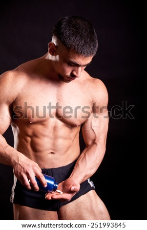 young bodybuilder taking steroids over black - stock photo