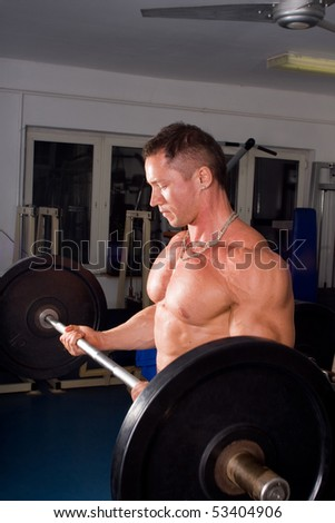 young Bodybuilder training his bicep - stock photo